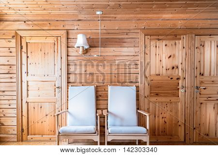 Pinewood interior wall, armchairs and doors, cabin cottage.