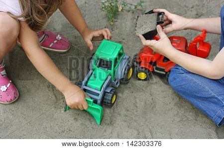 Children's outdoor play in the warmer time of the year. A boy with a girl playing with plastic building toy - excavator into the sand.