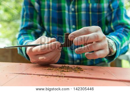 Close-up photo of man who fills his pipe with tobacco