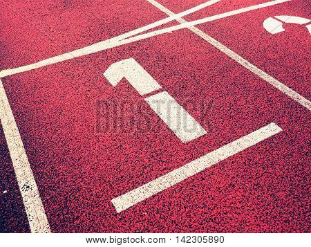 Number one. White athletic track number on red rubber racetrack texture of running racetracks in stadium