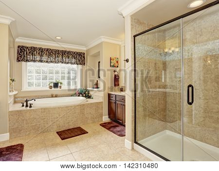 Master bathroom design with beige tile. View of luxurious bathtub shower and vanity cabinet. Northwest USA