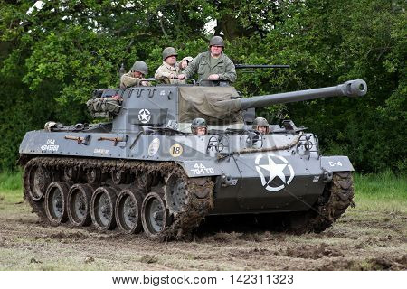 DENMEAD, UK - MAY 25: An ex US army Hellcat tank drives around the arena with reenactors on board at the end of a battle re-enactment at the Overlord show on May 25, 2014 in Denmead.