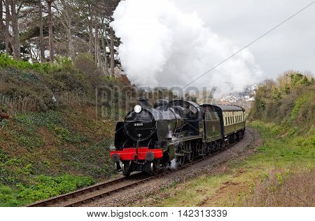 WATCHETT, UK - MARCH 27: A vintage SR U class steam locomotive leaves Watchett station on route to Bishops Lydeard during the spring WSR steam gala weekend on March 27, 2014 in Watchett