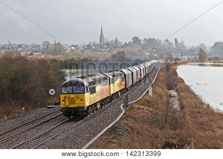 KINGS SUTTON, UK - FEBRUARY 10: Two Colas Rail locos haul a train of steels through flooded fields in Oxfordshire on February 10, 2014 in Kings Sutton. Colas Rail employ 4200 people over 11 countries