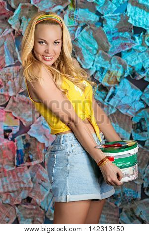 A smiling pretty girl with loose long blond hair is holding a bucket of paint with a brush in her hands in the unusual background of newspapers