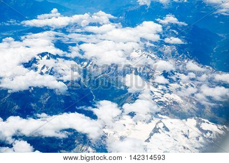 Alps with snow view through the white clouds