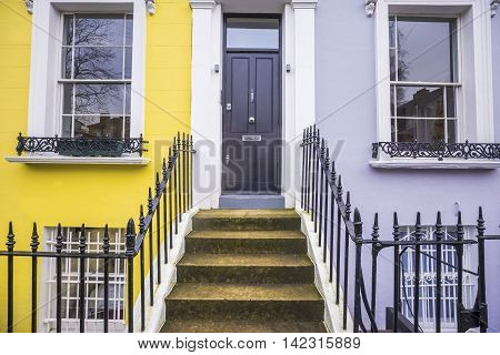 Yellow and grey painted traditional brick houses at Notting Hill district near Portobello road - London, UK