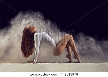 Dancer posing gracefully on the floor in a cloud of dust. Dancer posing bends back and figure on the floor. Dancer in a white bathing suit.