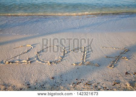 Year and number 2017 written on the sand on a beach