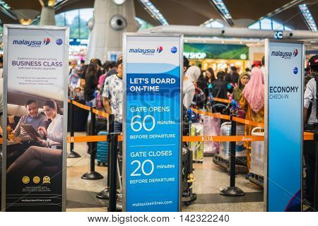 Kuala Lumpur, Malaysia - circa August 2016: Passengers at Malaysian Airlines check-in counter, Kuala Lumpur international airport, Malaysia. Malaysian Airlines is a flag carrier of Malaysia and is based in Kuala Lumpur.
