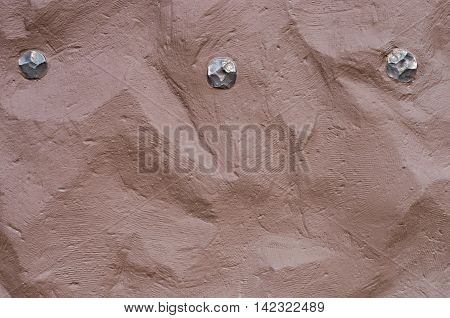 uneven surface of clay walls with iron rivets
