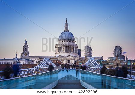 Londoners walking through Millennium Bridge with St.Paul's Cathedral at the background after sunset - London, UK