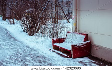red old couch standing in the street covered with snow
