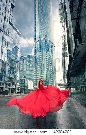 Full growth portrait of fashionable woman in red fluttering long dress on urban background