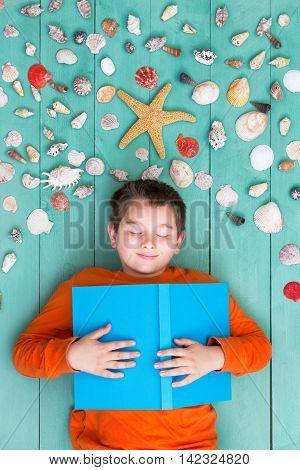 Cute Boy Laying Down Near Sea Shells