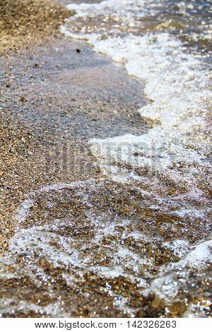 Sea foam gravel beach, clear sea wave
