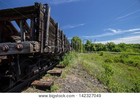 Abandoned wooden rail cars left to rot on a remote train track. Shot in horizontal orientation with a diminishing perspective and copy space.
