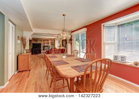 Red Dining Room Interior With Large Wooden Table And Chairs