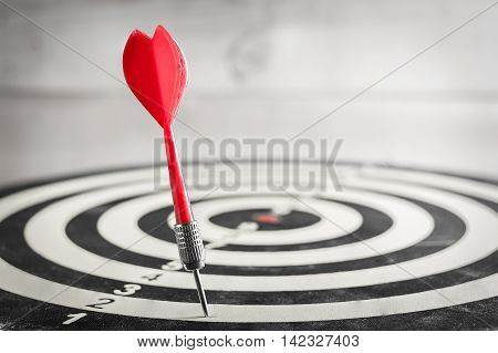 Red dart arrow missed in the target center of dartboard