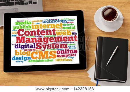 Colorful CMS tag cloud on a tablet computer in an office (3D Rendering)