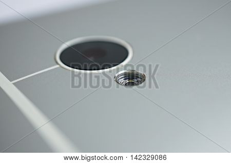 Macro detail of a LED diode at the back side of a silver brushed aluminum modern smart phone with shiny beveled edges
