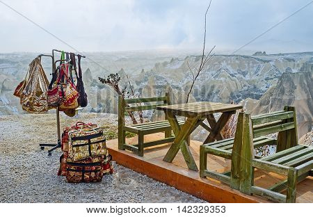 The holder with many colorful bags next to the tables of outdoor cafe in mountains of Cappadocia Turkey.