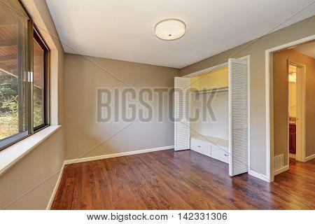 Empty Beige Room With Closet And Hardwood Floor.