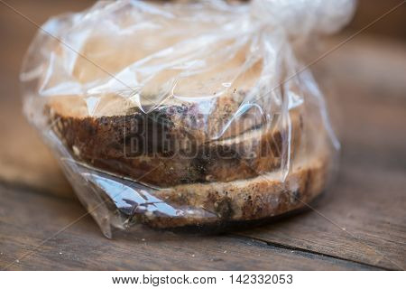 Close up of black fungus on expire organic french bread made from wheat flour raisin and multi grain seed on wooden table.