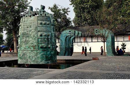 Langzhong Ancient City China - October 22 2013: An immense bronze temple bell set in a small pool with adjacent contemporary sculptures decorate a large open square