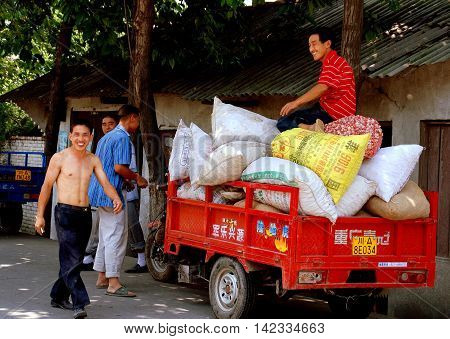 Sheng Pin China - June 24 2007: Farmers with a motorcycle cart filled with bags of dried garlic on its way to local markets