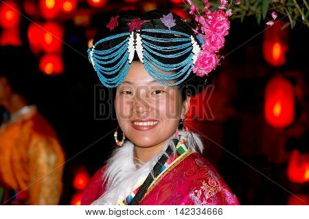 Lijiang China - April 19 2006: Woman wearing traditional Naxi clothing and a unique beaded headdress on Xing Hua Street