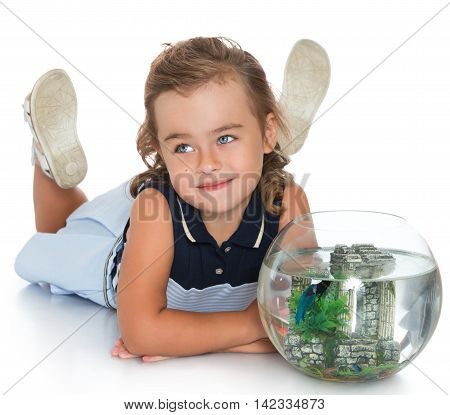 Beautiful little girl lying on the floor playing with the fish who swim in a fishbowl-Isolated on white background