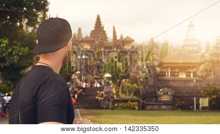 Young male backpacker tourist on Bali visits a Hindu temple on a volcano mountain - mother temple Besakih