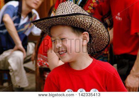 Longsheng / Guan Xi China - May 2 2006: Smiling Chinese boy wearing a straw cowboy hat in the Yao people hillside village of Ping-An