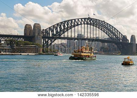 SYDNEY, AUSTRALIA - APRIL, 2016 : Fishburn ferry and other boats crossing under Sydney Harbour Bridge, steel arched bridge in Sydney, Australia on April 20, 2016.
