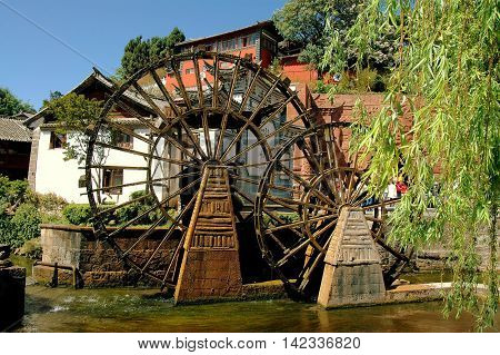 Lijiang China - April 19 2006: Two traditional Chinese wooden water wheels churn water in a stream flowing through Si Feng Square