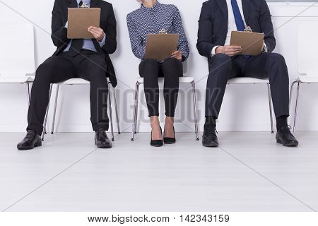 Cropped shot of a job candidates sitting on chairs and solving a test