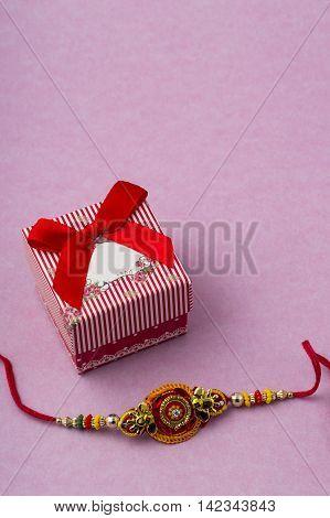 Indian festival: Raksha Bandhan background with Rakhi and Gift.