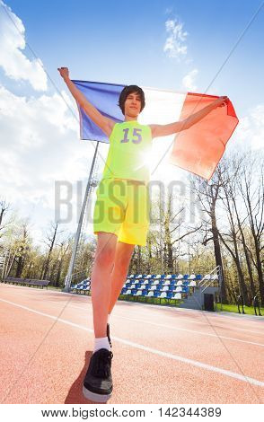 Full-length portrait of teenage boy in sportswear, running with flag of France outside on the track