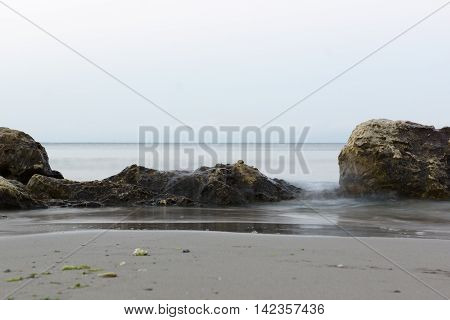 stone in the sea water under the oncoming wave