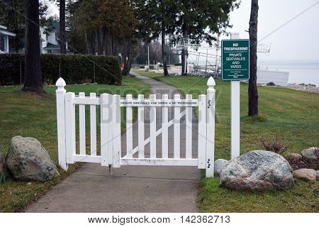 ROARING BROOK, MICHIGAN / UNITED STATES - DECEMBER 22, 2015: A white gate prevents people from Wequetonsing from trespassing onto the property of the Roaring Brook Association.