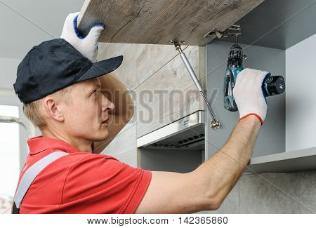Installation of kitchen. Workman fixes a hinge to a kitchen cabinet.