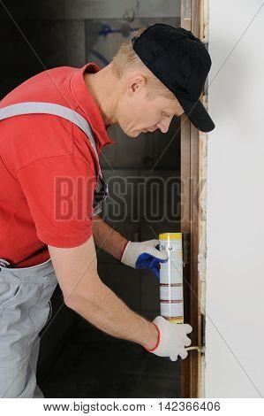 Installing door unit. Workman fixing the door frame using a mounting foam. poster