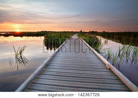 wooden bike path on water at sunset Netherlands
