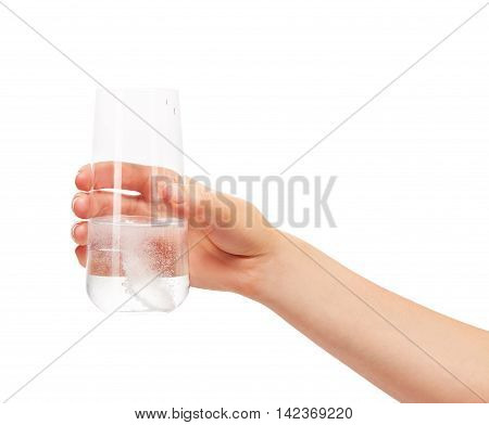 Close up of female hand holding clean transparent drinking glass with large white round effervescent tablet dissolving in water against white background. Clipping path for glass border included.