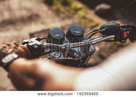 Cropped image of man riding motorcycle on road. Motorcyclist while driving focus on handle bar.