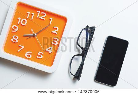 Modern Orange Clock Glasses and smart phonr