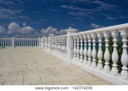 White decorative fence on the waterfront of the Anapa city resort on the Black Sea coast. Blue cloudy sky water with an emerald hue green tree leaves. Selective Focus on foreground.