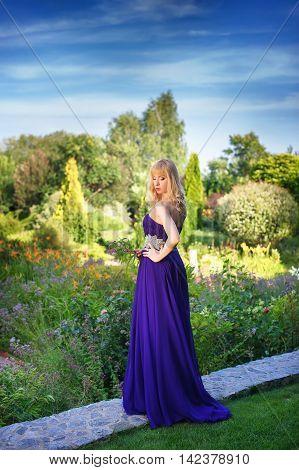 Portrait of beautiful woman dressed in evening gown. Blonde Beautiful woman in long purple dress like princess in green garden. Woman holding bouquet of wildflowers.