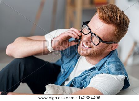 Always in touch. Cheerful delighted handsome man smiling and talking on cell phone while sitting on the settee